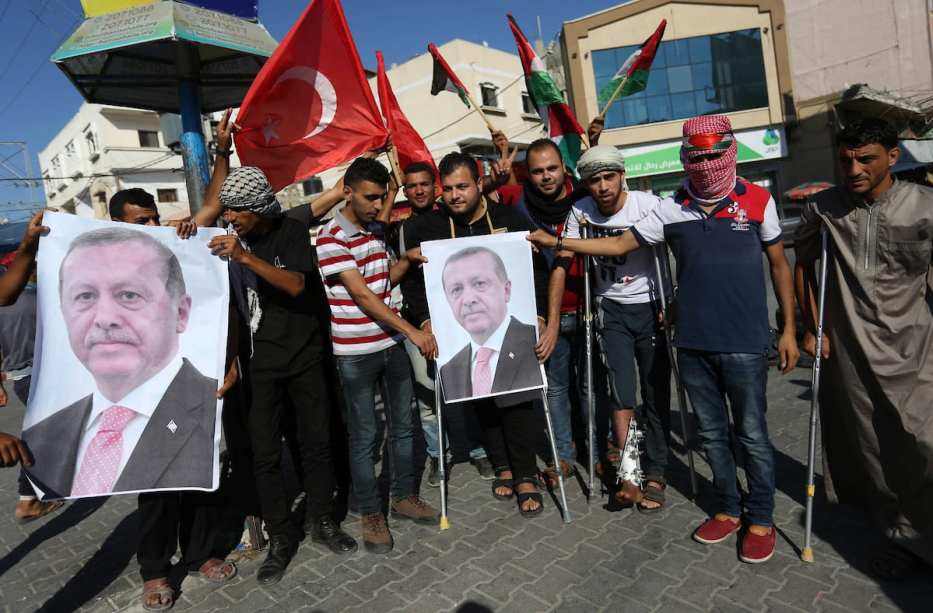 Palestinians who were wounded by Israeli troops during clashes hold portraits of Turkish President Recep Tayyip Erdogan and celebrate after Erdogan had won in Turkey's presidential and parliamentary elections, in Khan Younis in the southern Gaza Strip on 25 June, 2018 [Ashraf Amra/Apaimages]