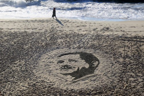 A Palestinian artist Osama Sbeata draws the portrait of Turkish President Recep Tayyip Erdogan on sand to celebrate the results of the Turkish presidential and parliamentary elections on Gaza Sea on 26 June, 2018 [Abed Abu Ryash/Apaimages]