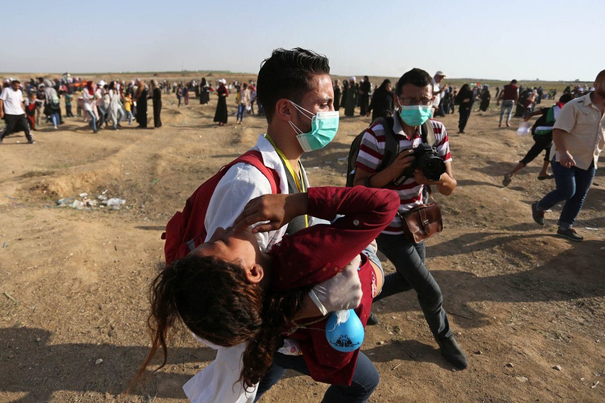 "Palestinian medical staff carry a wounded woman during a protest within the ""Great March of Return"" demonstrations near Israel-Gaza border in Gaza City, Gaza on 3 July, 2018 [Ashraf Amra/Anadolu Agency]"