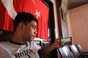 """A Palestinian young Emin Selim (20) watches the moments of getting shot as he speaks to press in front of Turkish flag at his home after he was shot by Israeli army while he was waving a Turkish flag during a protest within the """"Great March of Return"""" demonstrations near Israel-Gaza border, at Shujaiyya neighbourhood of Gaza City, Gaza on 4 July, 2018 [Mustafa Hassona/Anadolu Agency]"""