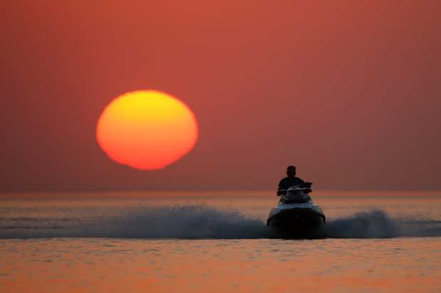 A man rides a jet ski through coastal side during a sunset at the second public beach of Lake Van, in Van, Turkey on 12 July, 2018 [Özkan Bilgin/Anadolu Agency]