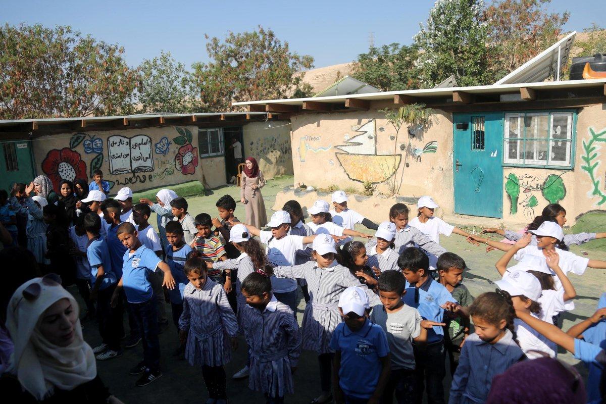 Palestinian Bedouin children wait in line before they enter classrooms at the only school in the region 'Itarat School' in Khan al-Ahmar region of Jerusalem on 16 July, 2018 [İssam Rimawi/Anadolu Agency]