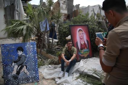 A man poses for a photo with two paintings among the wreckage of buildings during an exhibition that held by a group of Palestinian artists, after Israeli forces hit the area with airstrikes at the Art and Craft Village in Gaza City, Gaza on 16 July, 2018 [Hassan Jedi/Anadolu Agency]
