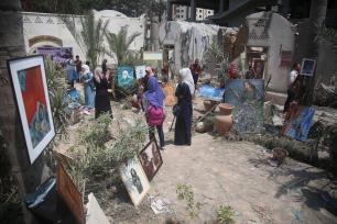 People take a look at paintings among wreckage of buildings during an exhibition that held by a group of Palestinian artists, after Israeli forces hit the area with airstrikes at the Art and Craft Village in Gaza City, Gaza on 16 July, 2018 [Hassan Jedi/Anadolu Agency]