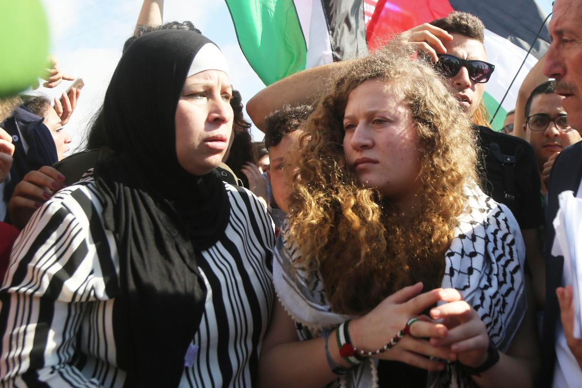 "Palestinian teenager Ahed al-Tamimi (C), who was awarded the ""Hanzala Award for Courage"" in Turkey, is released with her mother Nariman Tamimi (not seen) after 7 months in prison at Israeli check point in Nabi Saleh district of Ramallah, West Bank on 29 July, 2018 [Issam Rimawi/Anadolu Agency]"