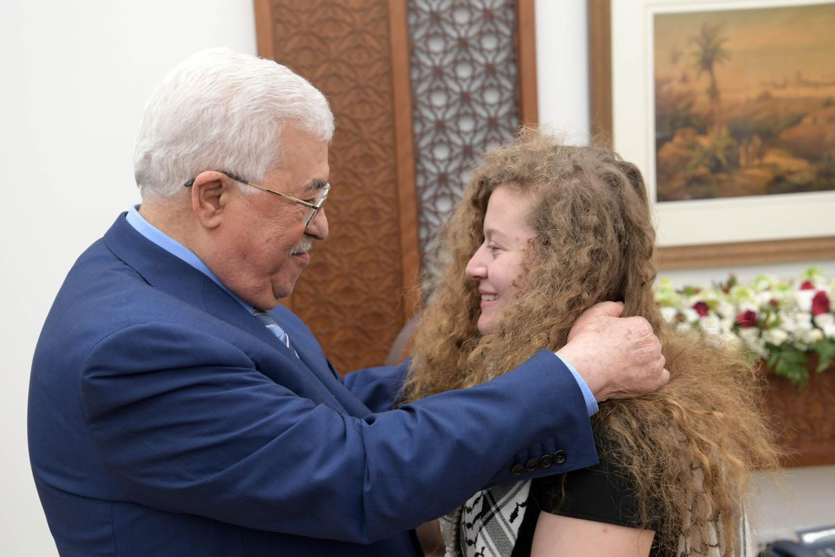 """Palestinian President Mahmoud Abbas (L) welcomes Palestinian teenager Ahed al-Tamimi (R), who was awarded the """"Hanzala Award for Courage"""" in Turkey, after she was released from Israeli prison along with her mother at the Presidential Office in Ramallah, West Bank on 29 July, 2018 [Palestinian Presidency Handout/Anadolu Agency]"""