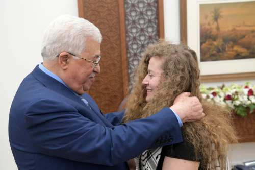 "Palestinian President Mahmoud Abbas (L) welcomes Palestinian teenager Ahed al-Tamimi (R), who was awarded the ""Hanzala Award for Courage"" in Turkey, after she was released from Israeli prison along with her mother at the Presidential Office in Ramallah, West Bank on 29 July, 2018 [Palestinian Presidency Handout/Anadolu Agency]"