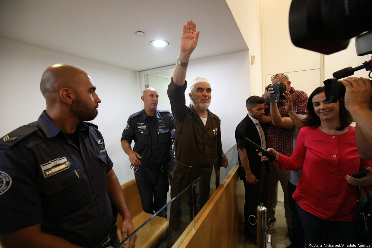 Leader of the Northern Branch of the Islamic Movement in Israel, Sheikh Raed Salah (C) raises his hand as he appears in court on 5 July 2018 [Mostafa Alkharouf/Anadolu Agency]