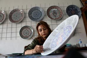 36-year-old tile art artist Gulseren Oztugcu is seen drawing pattern on the art of tile-making on 7 August, 2018 in Kutahya, Turkey [Muharrem Cin/Anadolu Agency]