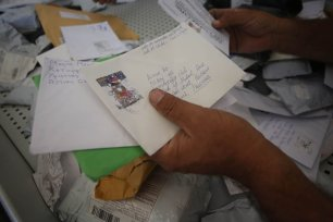 Palestinian postal worker shows an undelivered mail blocked by Israel for years at the Palestinian central international exchange post office in Jericho, West Bank [Issam Rimawi/Anadolu Agency]