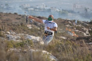 A Palestinian protester throws rock in response to Israeli intervention during a demonstration held against Jewish occupation over Palestinians' fields in Ras Karkar village of Ramallah, West Bank on 30 August, 2018 [Issam Rimawi/Anadolu Agency]