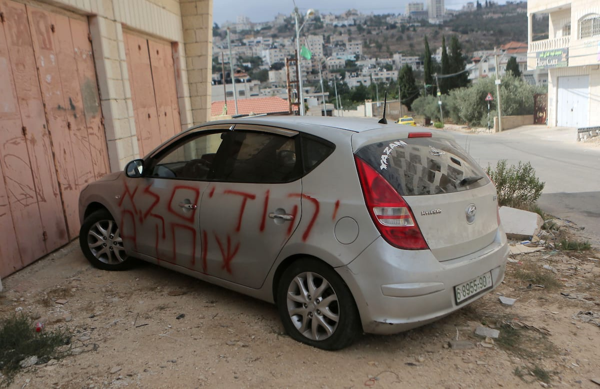 "Settlers sprayed racist slogans that read in Hebrew ""Jews will not be silent"" and slashed the tyres of a Palestinian resident's car in the occupied West Bank town of Singel north of Ramallah, on 27 August, 2018 [Shadi Hatem/Apaimages]"