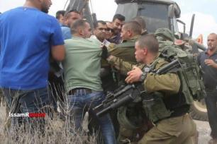 Palestinians attemp to stop Israeli Jewish settlers from razing private Palestinian lands in the village of Ras Karkar, West Bank [Issam al Rimawi]