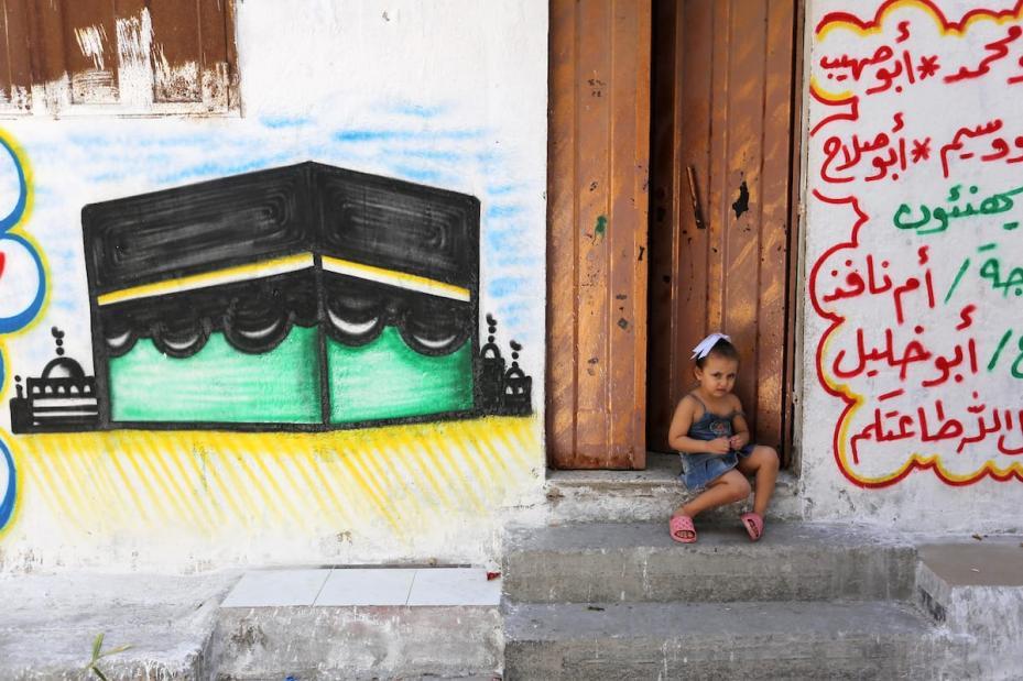 A Palestinian refugee girl sits outside her family house at Al-Shati refugee camp, in Gaza City on 3 September, 2018 [Ashraf Amra/Apaimages]