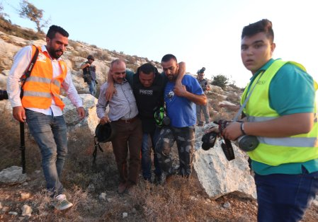 Issam Rimavi (C), a photojournalist of the Turkey's Anadolu Agency, is being carried away by colleagues after getting injured by the intervention of Israeli forces while covering demonstrations in the village of Ras Karkar near Ramallah, West Bank on September 04, 2018. AFP photographers Abbas Mumini and English Joe Dyke were also hit in the feet after Israeli soldiers opened fire with plastic bullets. ( Shadi Hatem - Anadolu Agency )