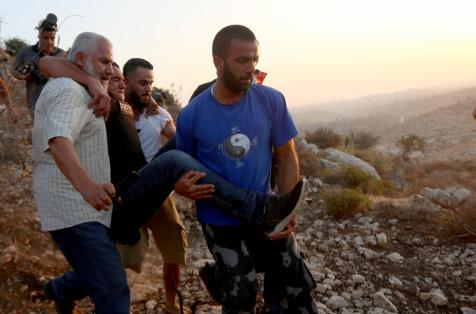Issam Rimavi (3rd L), a photojournalist of the Turkey's Anadolu Agency, is being carried away by colleagues after getting injured by the intervention of Israeli forces while covering demonstrations in the village of Ras Karkar near Ramallah, West Bank on September 04, 2018. AFP photographers Abbas Mumini and English Joe Dyke were also hit in the feet after Israeli soldiers opened fire with plastic bullets. ( Shadi Hatem - Anadolu Agency )