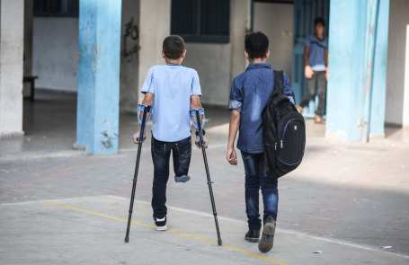 """Palestinian student Mohammed Abu Hussain (L) from Gaza, who lost his leg after being shot by an Israeli sniper during """"Great March of Return"""" demonstrations, walks with his crutches at the playground of his school in Gaza City, Gaza on September 03, 2018. ( Ali Jadallah - Anadolu Agency )"""