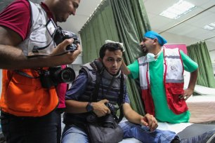 Wounded protesters receive treatment after Israeli forces attacked them with tear gas canisters during an anti-occupation rally near the Gaza on 18 September 2018 [Ramez Habboub/Anadolu Agency]