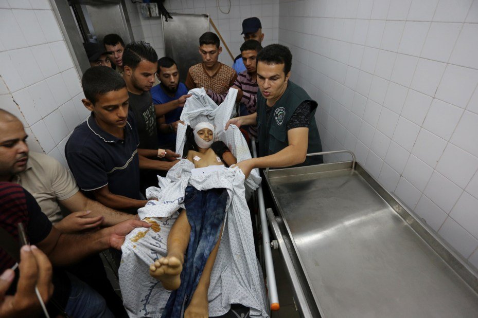 """Palestinian paramedics carry a body of a child after he was shot dead by Israeli forces during demonstrations at the Israeli border within the """"Great March of Return"""", at the morgue of European Hospital in Khan Yunis, Gaza on September 28, 2018. ( Ashraf Amra - Anadolu Agency )"""