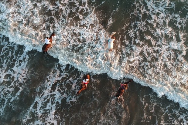 Horse-riding trainers walk with their horses at a beach during sunset in Turkey on 5 September 2018 [Ozan Efeoğlu/Anadolu Agency]