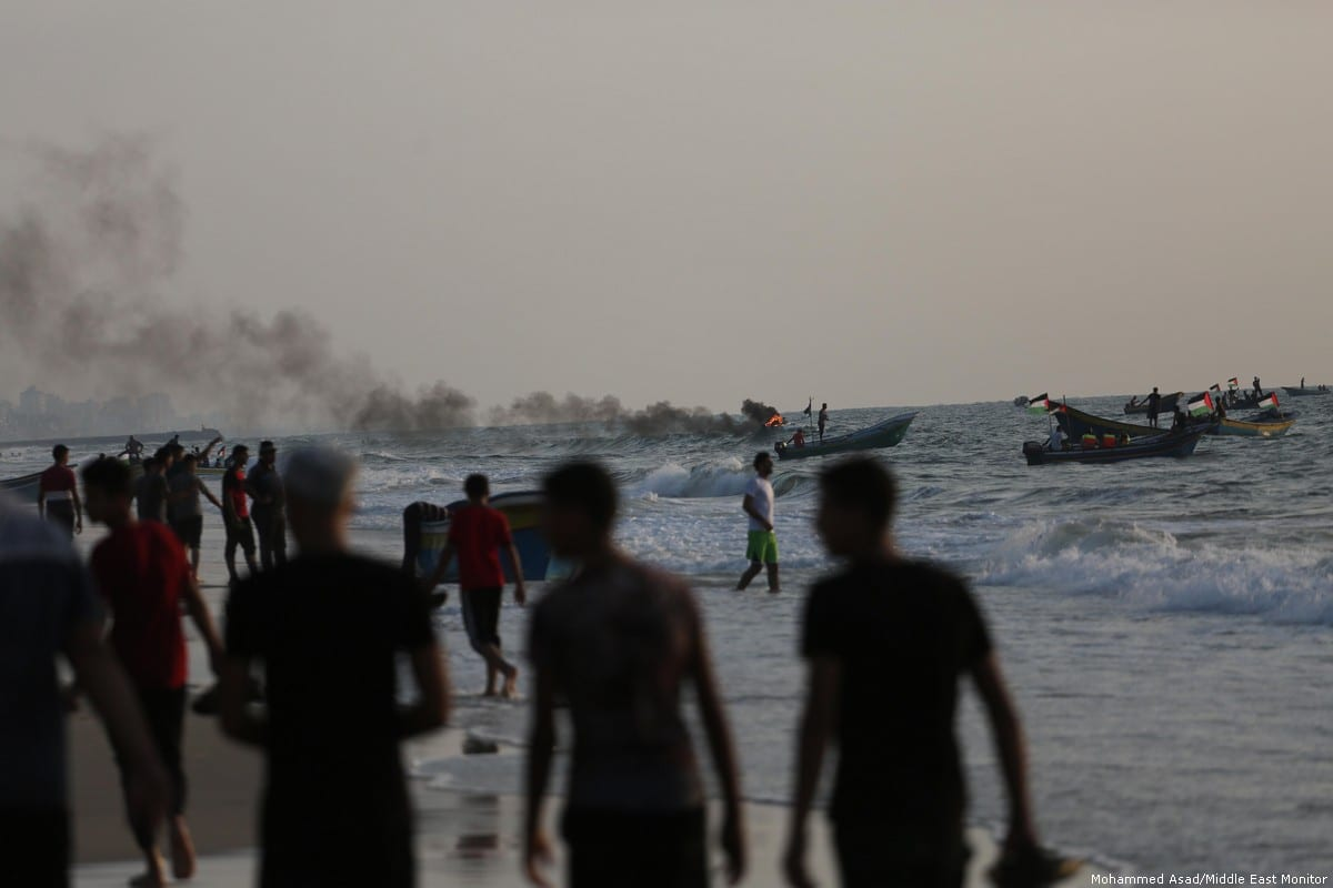 Smoke rises from Gaza's coastal waters after Israeli naval ships fired gas canisters and shot at demonstrators [Mohammed Asad/Middle East Monitor]