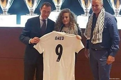 Ahed Tamimi met with Emilio Butragenio, a former striker for Real Madrid, who gave her a team jersey with her name and number nine printed on its back [Ma'an News Agency]