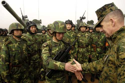 Chairman of the US Joint Chiefs of Staff, Marine Gen. Peter Pace, shakes hands with Chinese tanker soldiers with the People's Liberation Army at Shenyang training base, China, March 24, 2007. [US DoD / Staff Sgt. D. Myles Cullen]
