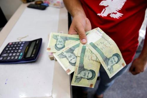 A vendor inspects Iranian rials at a currency exchange shop in Baghdad, Iraq August 8, 2018. REUTERS/Khalid Al-Mousily/File Photo