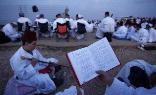 Pictured: Samaritans read and sit atop the mountain during celebrations of Sukkot West Bank, 23 October 2018 [Shadi Jarar'ah/Apaimages]
