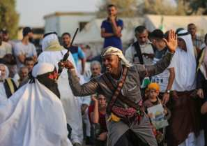 Palestinians perform folk dance during the Palestinian and Najaf Bedouin Tribes Festival within the 'Great March of Return' demonstrations near Gaza border, in Gaza City, Gaza on 2 October 2018 [Mustafa Hassona/Anadolu Agency]