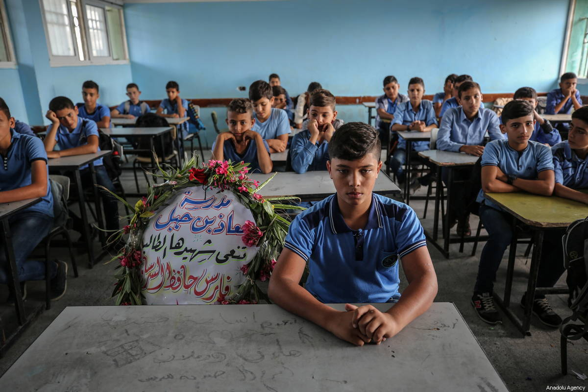 """A wreath lays on the seat of Faris Hafez al-Sarasawi, 12 years old Palestinian child who was killed by Israeli forces in """"Great March of Return"""" demonstrations, during a remembering by his classmates and teacher at Muaz bin Jabal Elementary School in Shuja'iyya neighborhood of Gaza City, Gaza on October 06, 2018 [Ali Jadallah / Anadolu Agency]"""