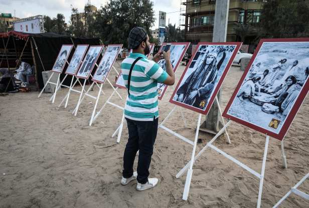 A man takes a picture of the displayed photos in Gaza, 11 October 2018 [Mustafa Hassona/Anadolu Agency]