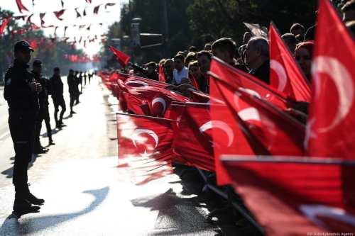 People hold Turkish flags during a ceremony marking the 95th anniversary of Republic Day in Istanbul, Turkey on 29 October 2018 [Elif Öztürk/Anadolu Agency]