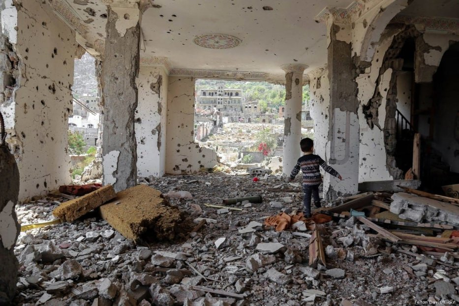 A Yemeni child walks among the rubble of a home after it was destroyed by airstrikes in Yemen [Felton Davis/Flickr]