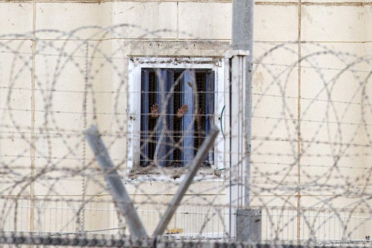 Prisoners gesture from their cell Hasharon, an Israeli prison [JACK GUEZ/AFP/Getty Images]