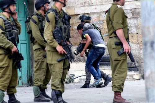 Israeli soldiers detain a Palestinian youth in the West Bank city of Hebron, on 22 September 2017 [Mamoun Wazwaz/Apaimages]
