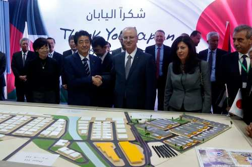 Palestinian Prime Minister Rami Hamdallah stands next to Japan's Prime Minister Shinzo Abe at the Jericho Agro Industrial Park (JAIP) on a visit to the West Bank on 2 May 2018. [Wisam Hashlamoun/Apaimages]