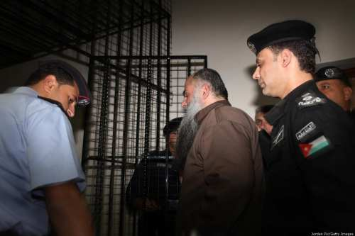 A prisoner is escorted to his cell on September 24, 2014 in, Jordan. [Jordan Pix/ Getty Images]