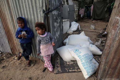 Palestinian children stand next to bags of food aid provided by the UN agency for Palestinian refugees at their family home in the Gaza Strip on 24 January 2018 [Said Khatib/AFP/Getty Images]