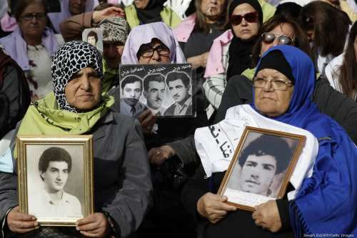 Lebanese citizens carry pictures of family who disappeared during the Lebanese civil war in 1975, in Beirut, Lebanon on 28 November 2018 [Joesph Eid/AFP/Getty Images]