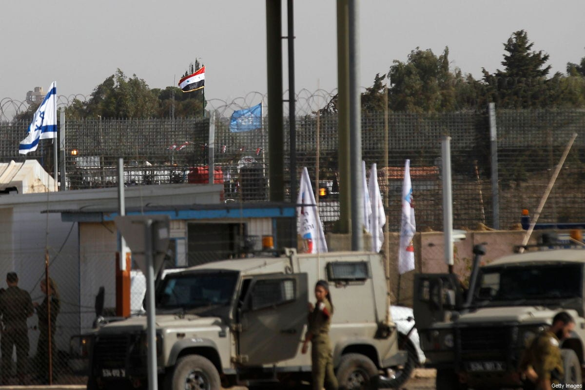The Israeli (L) and Syrian (C) flags flutter at the crossing between the Israeli-controlled side of the annexed Golan Heights and Syria after the reopening of the only crossing between the two sides near Quneitra on October 15, 2018 [JALAA MAREY/AFP/Getty Images]