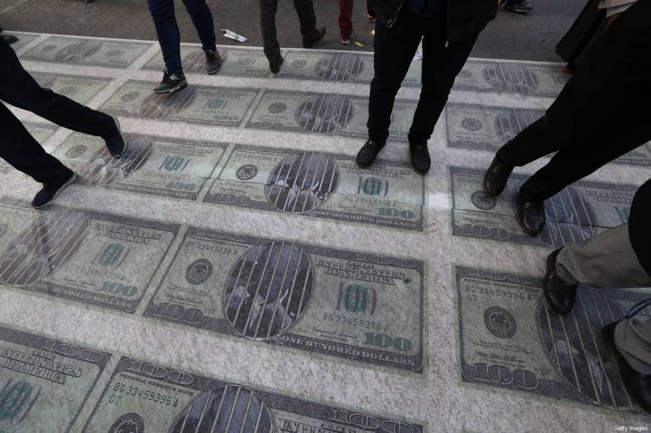 Iranian protesters trample on huge prints of US 100 dollar banknote images during a demonstration outside the former US embassy in the capital Tehran on November 4, 2018, to mark the anniversary of its storming by student protesters that triggered a hostage crisis in 1979 [ATTA KENARE/AFP/Getty Images]