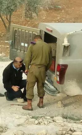 Palestinian officials can be seen helping Israeli occupation soldiers to fix their military vehicle in Hebron on 14 November 2018 [Shehab News Agency/Facebook]