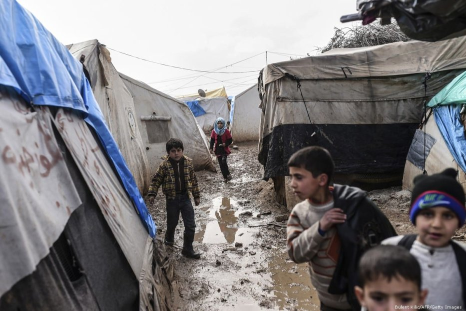 Syrian children walk in the mud after a heavy rain fell at a refugee camp in Syria on 6 February 2016 [Bulent Kilic/AFP/Getty Images]