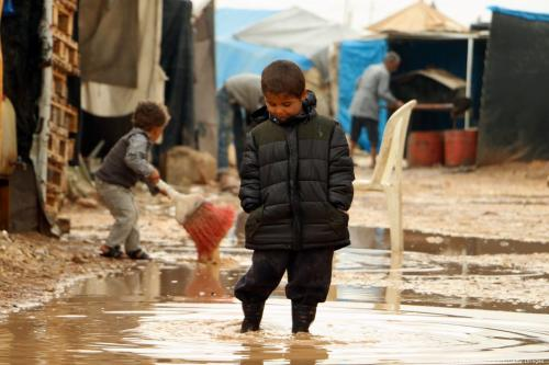 Displaced Syrian children play in the mud following rain at the Bab al-Salama camp, set up outside the Syrian city of Azaz on 30 October 2016 [SALEH ABO GHALOUN/AFP/Getty Images]
