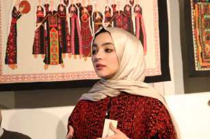 Jehan Alfarra stands to speak on some of the pieces displayed at the P21 gallery on 11 December 2018 [Middle East Monitor]