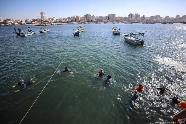 Palestinian volunteer divers clean up Port of Gaza from waste materials in Gaza City, Gaza on 4 December 2018 [Mustafa Hassona/Anadolu Agency]