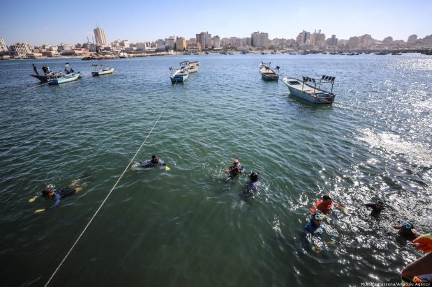 Palestinian volunteer divers clean up Port of Gaza from waste materials in Gaza City, Gaza on 4 December 2018 [Mustafa Hassona/Anadolu Agency]