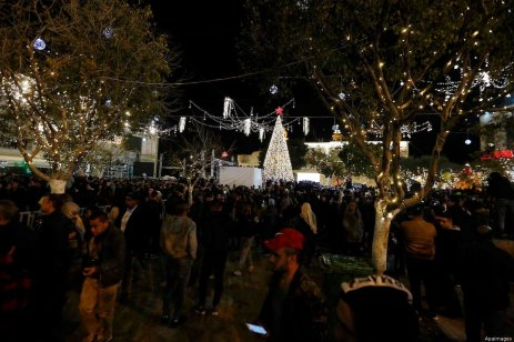 Palestinian Christians watch as fireworks light the sky to mark the lighting of a Christmas tree on Manger Square near the Church of the Nativity in the biblical West Bank town of Bethlehem on 1 December 2018 [Wisam Hashlamoun/Apaimages]