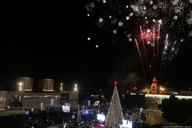 Fireworks light up the sky as streets and avenues near the Church of the Nativity, which is traditionally considered to be located over the cave that marks the birthplace of Jesus, are illuminated with Christmas lights in Bethlehem on 1 December 2018. [Issam Rimawi /Anadolu Agency]